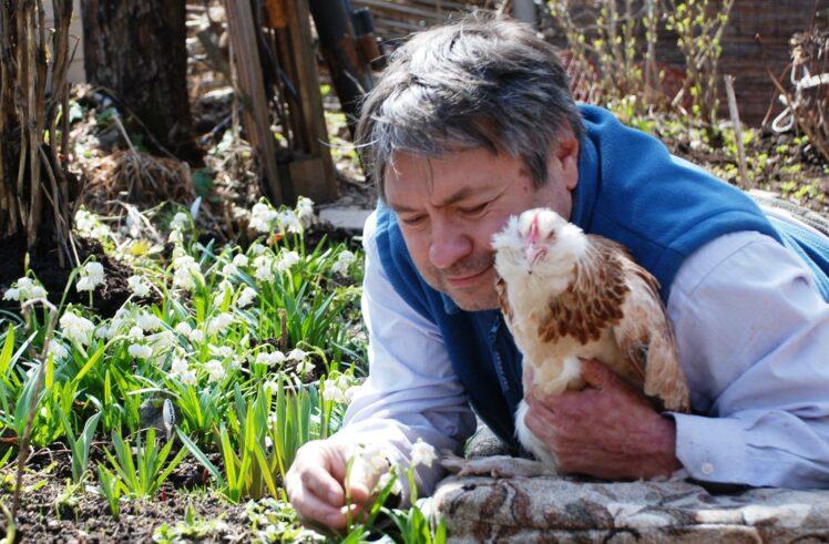 мужчина держит на руках курицу